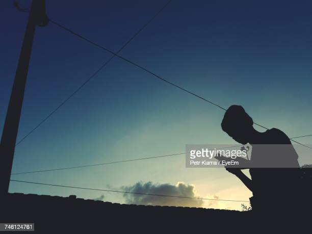 Silhouette Of A Woman Using A Mobile Phone