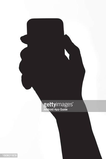 A silhouette of a woman's hand holding a Samsung Galaxy Ace smartphone during a studio shoot for Android App Guide February 11 2011