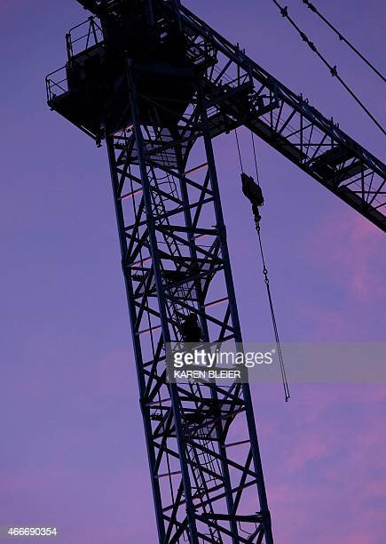 A silhouette of a worker is seen as he climbs to his perch high above a building under construction March 18 2015 in Washington DC AFP PHOTO / KAREN...
