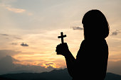 Silhouette of a young girl holding a crucifix to God Morning with beautiful sunrise, Symbol of Faith. Christian life prayer crisis to god.