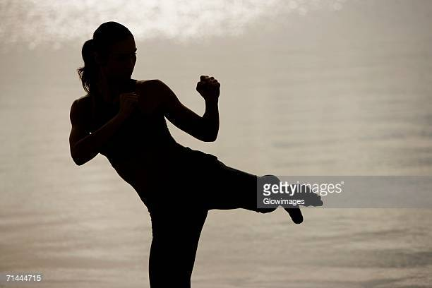 Silhouette of a young woman practicing martial arts on the beach