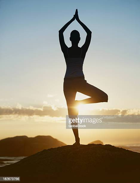 Silhouette of a young woman practicing yoga at sunrise