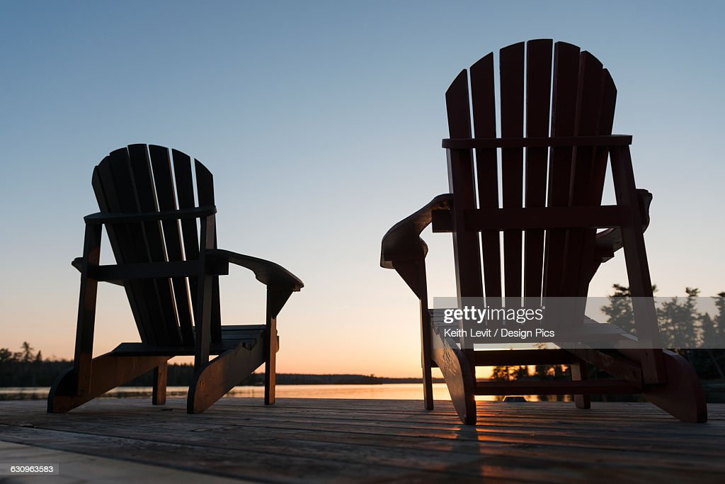 Silhouette Of Adirondack Chairs On A Wooden Dock Along A Lake At Sunset :  Stock Photo
