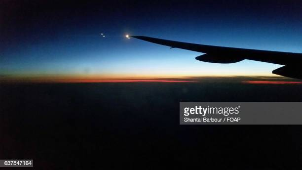 Silhouette of airplane flying at sunset