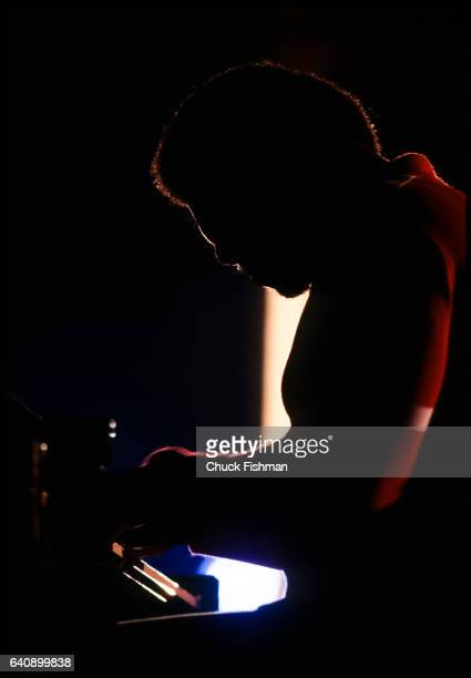 Silhouette of American Jazz musician McCoy Tyner plays piano as he performs during the New Orleans Jazz Heritage Festival at the Fair Grounds Race...