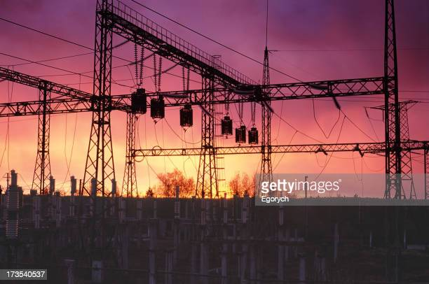 A silhouette of an energy station with a sunset background