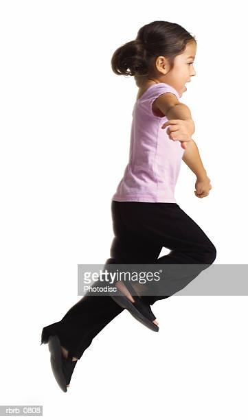 silhouette of an ethnic female child in black pants and a purple shirt as she skips forwards