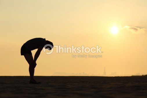 Silhouette of an exhausted sportsman at sunset : Stock Photo