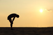 Silhouette of an exhausted sportsman at sunset with the horizon in the background