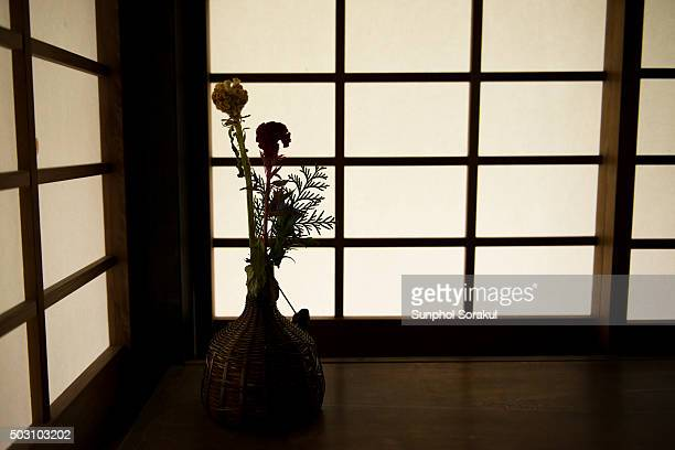 Silhouette of an Ikebana or flower arranged in a vase against the grid of Shoji wall