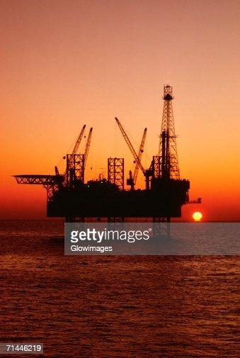 Silhouette of an oil drilling rig at dusk, Mediterranean Sea, Tunisia