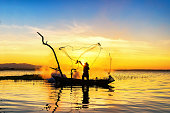 Silhouette of asian fisherman on wooden boat ,fisherman in action throwing a net for catching freshwater fish in nature river