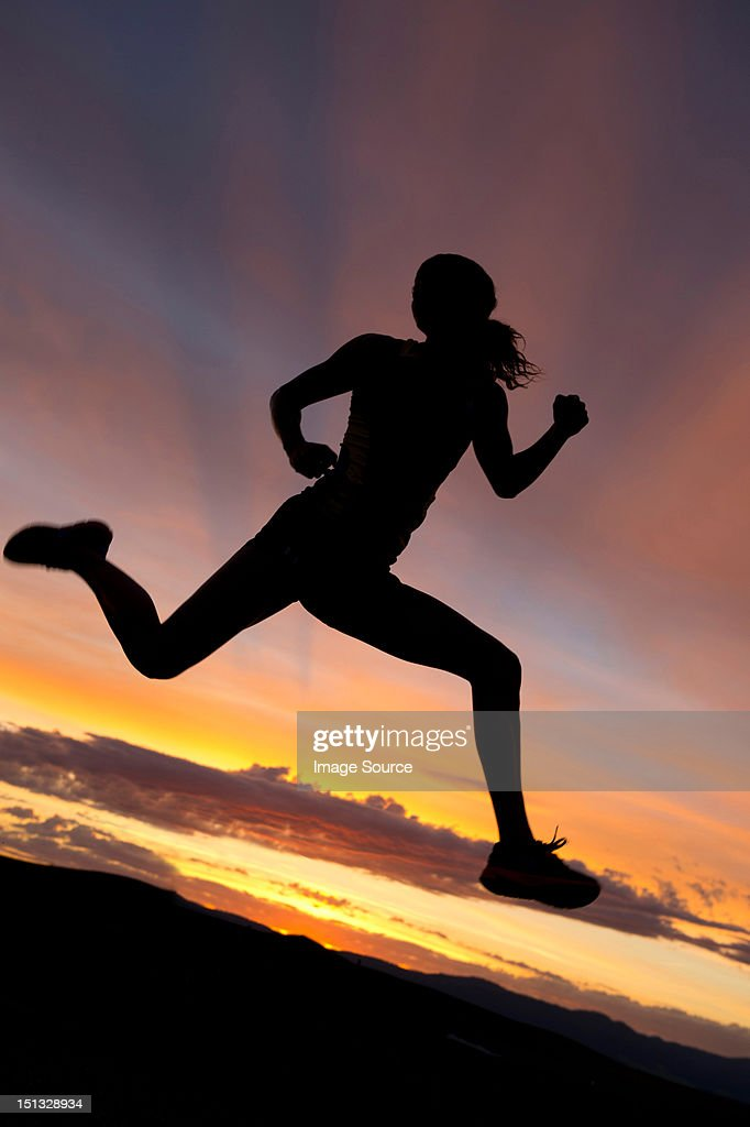 Silhouette of athlete jumping against sunset : Stock Photo