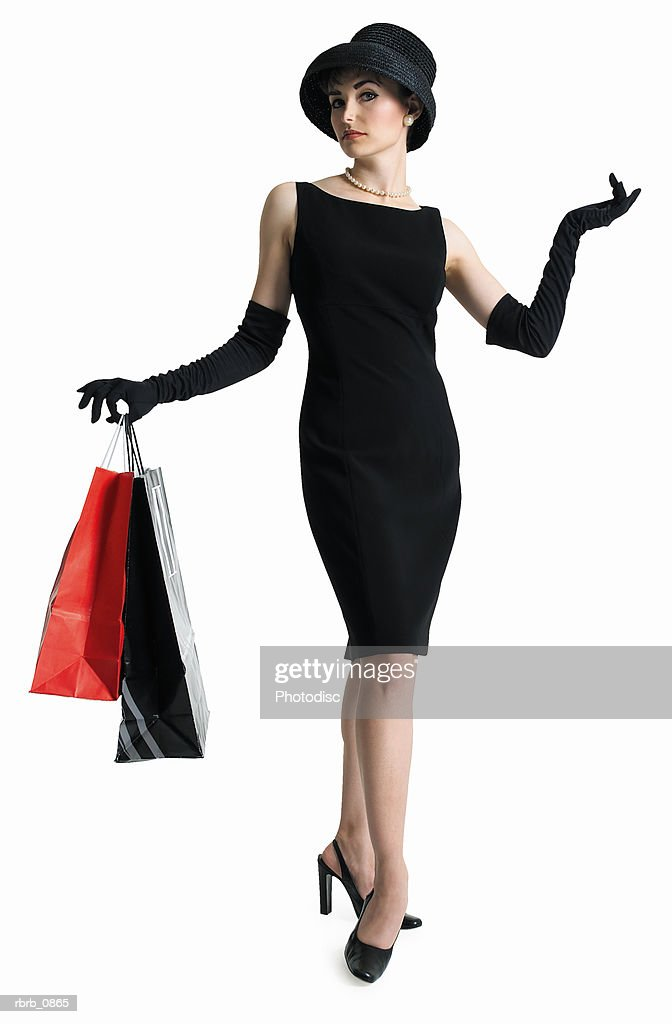 silhouette of attractive sophisticated caucasian woman in black dress hat as she holds shopping bags : Stock Photo