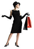 silhouette of attractive sophisticated caucasian woman in black dress hat as she holds shopping bags