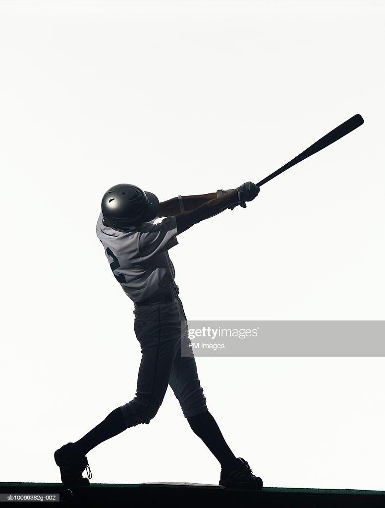 Silhouette of baseball batter swinging bat, side view