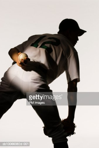 Silhouette of baseball pitcher holding ball behind back, rear view, close-up