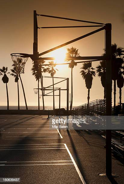 Silhouette of basketball hoop on court