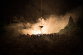 Silhouette of blurred giant scale of justice behind crowd at night with foggy fire background. Selective focus