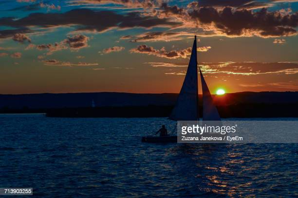 Silhouette Of Boat In Sea At Sunset