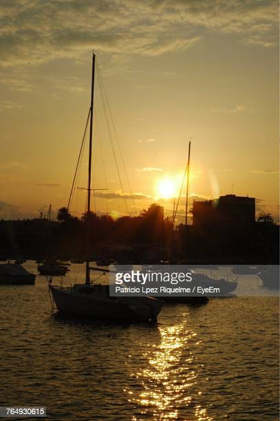 Silhouette Of Boats In River During Sunset
