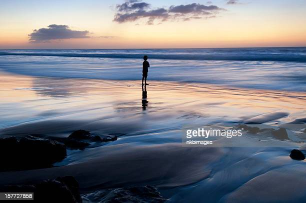 Silhouette of boy by the ocean at sunset