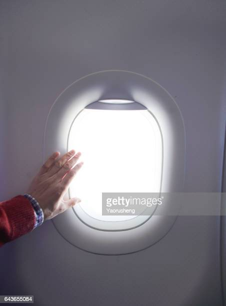Silhouette of boy hand over the window of airplane