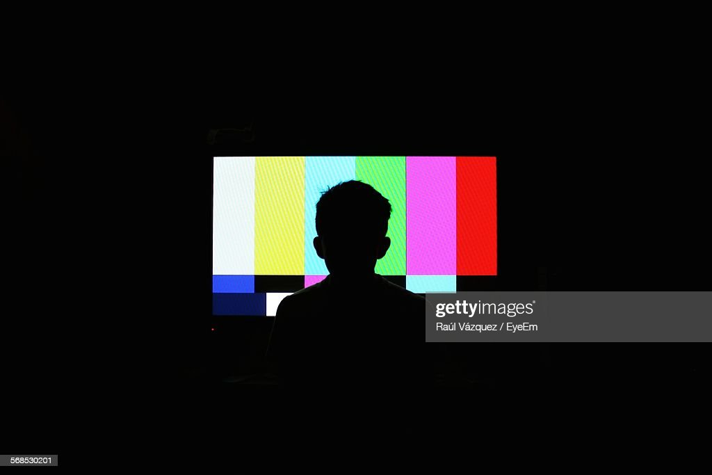 Silhouette Of Boy In Front Of Television Screen