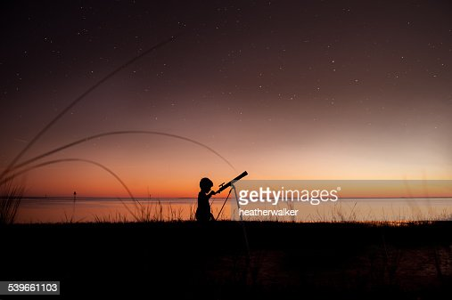 USA, Florida, Silhouette of boy looking at stars through telescope