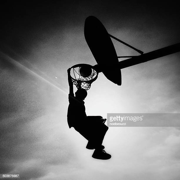 Silhouette of boy playing basketball scoring slam dunk