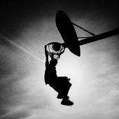 Silhouette of boy scoring slam dunk