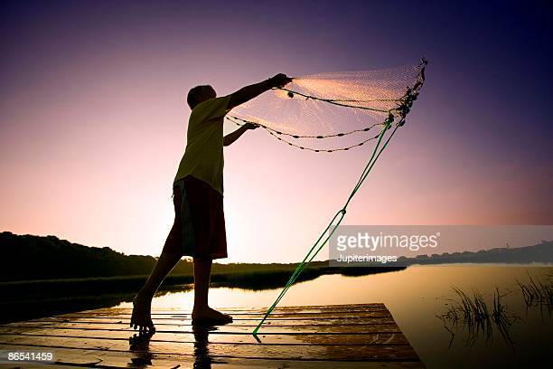Silhouette of boy throwing out fishing net