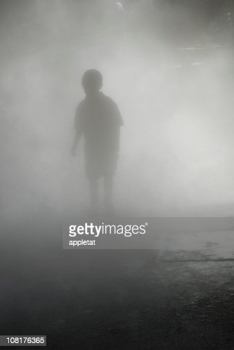 Silhouette of Boy Walking Through Heavy Fog