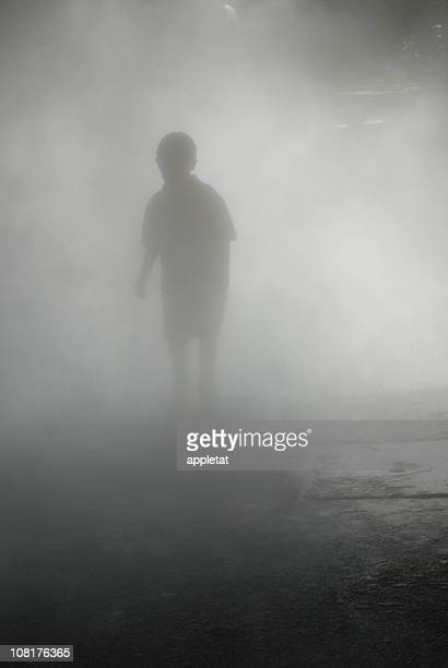 Silhouette of Boy Walking Through Heavy Fog