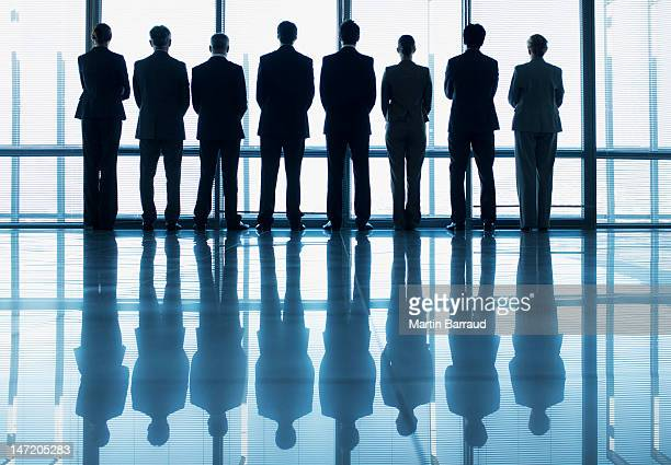 Silhouette of business people in a row looking out lobby window