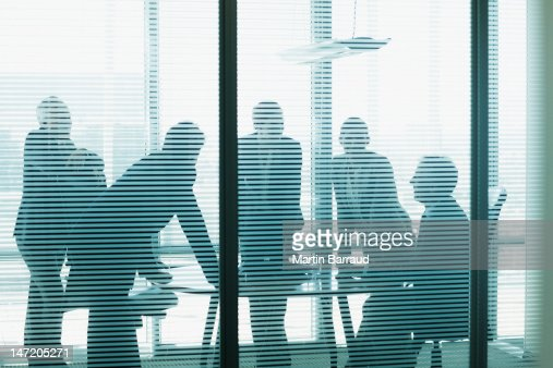 Silhouette of business people leaning on table in conference room : Stock Photo