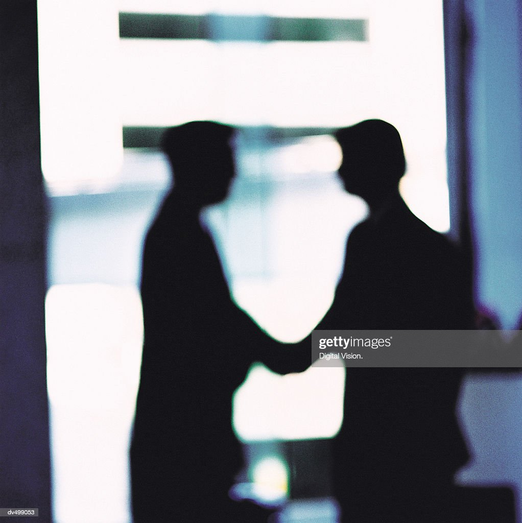 Silhouette of Business People Shaking Hands : Stock Photo