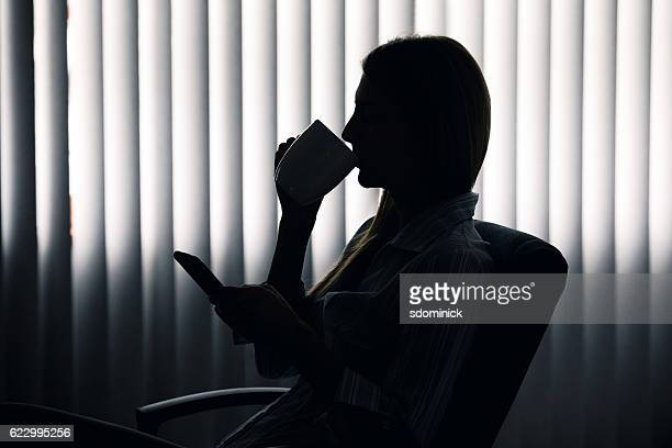 Silhouette Of Business Woman Sipping Coffee
