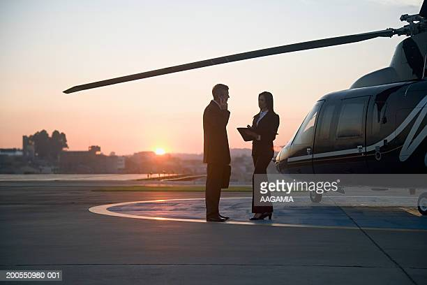 Silhouette of businessman and woman standing by helicopter, side view