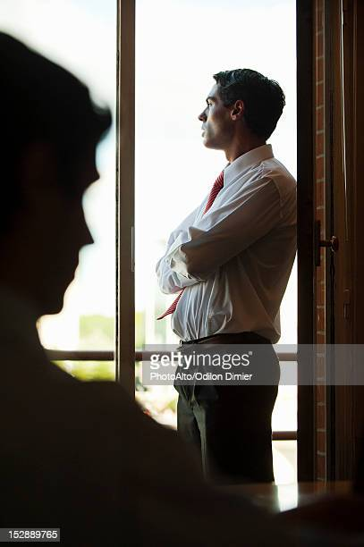 Silhouette of businessman standing by window