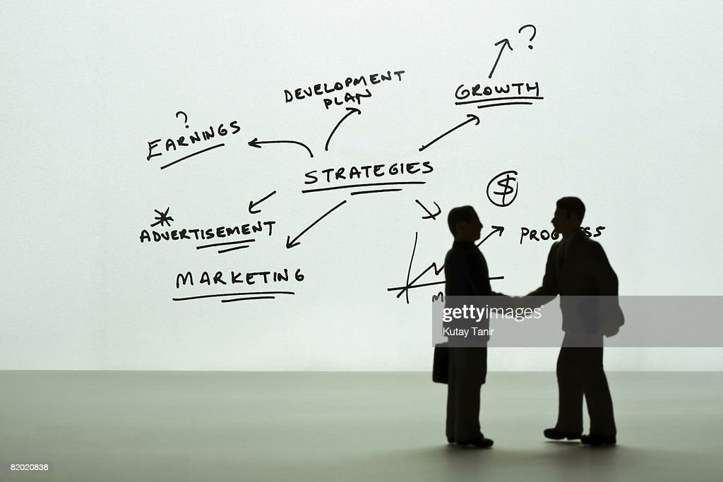 Silhouette of businessmen figurines shaking hands, diagram in background. (Focus on background) : Stock Photo