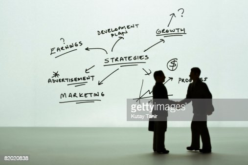 Silhouette of businessmen figurines shaking hands, diagram in background. (Focus on background) : Bildbanksbilder