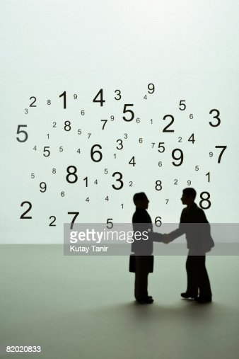 Silhouette of businessmen figurines shaking hands, numbers in background. (Focus on background) : Stock Photo