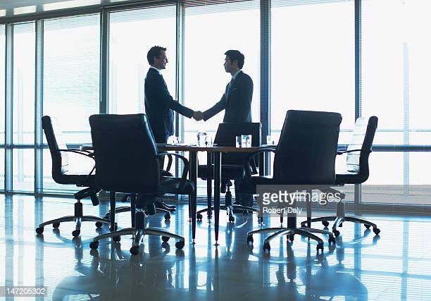 Silhouette of businessmen shaking hands in conference room