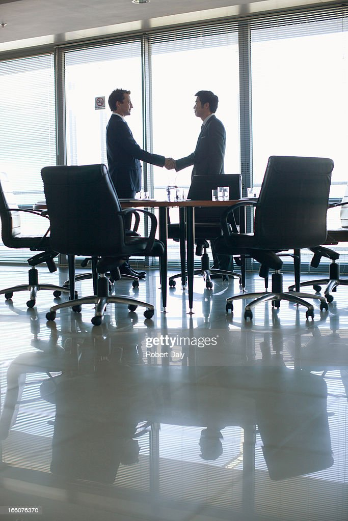 Silhouette of businessmen shaking hands in conference room : Stock Photo