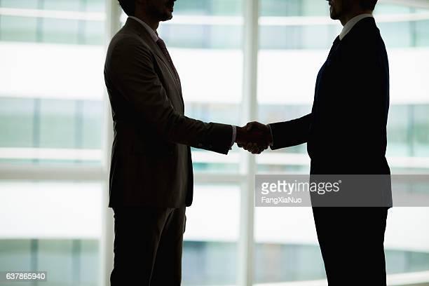 Silhouette von Geschäftsleuten beim Händeschütteln im Büro