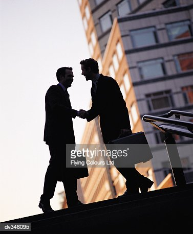 Silhouette of businessmen shaking hands : Stock Photo