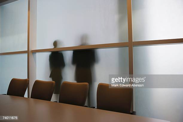 Silhouette of businesspeople through frosted glass wall