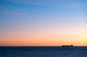 Silhouette  of cargo ship on the horizon viewed from bay with rock