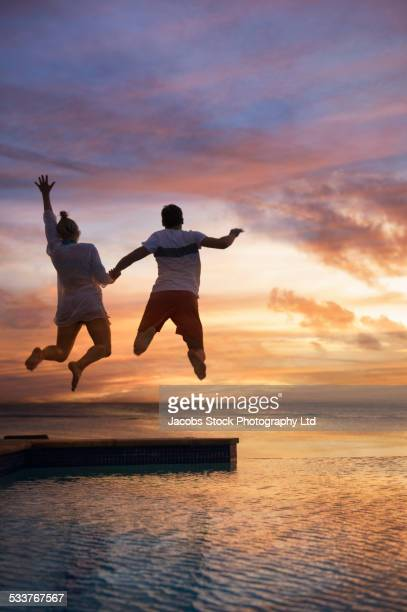 Silhouette of Caucasian couple jumping into swimming pool at sunset